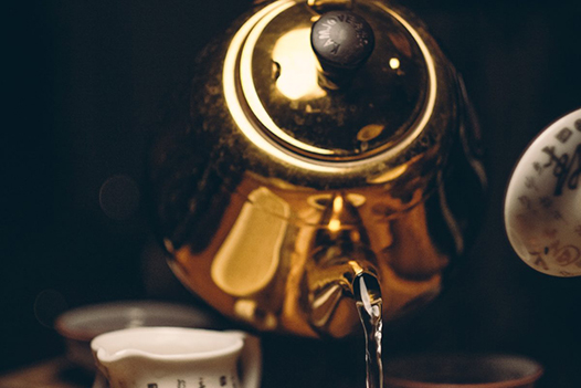 Person holding a gold teapot